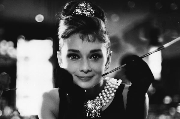 "Audrey Hepburn's classic style and fashionable pearls in the iconic film, ""Breakfast at Tiffany's."""
