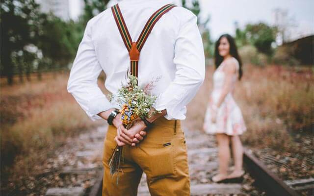 Man holding flowers behind his back to surprise girlfriend