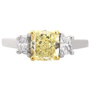 three stone engagement ring set with a yellow diamond